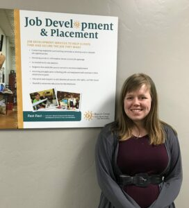 Elena Smiling Next to Beacon Job Placement Sign